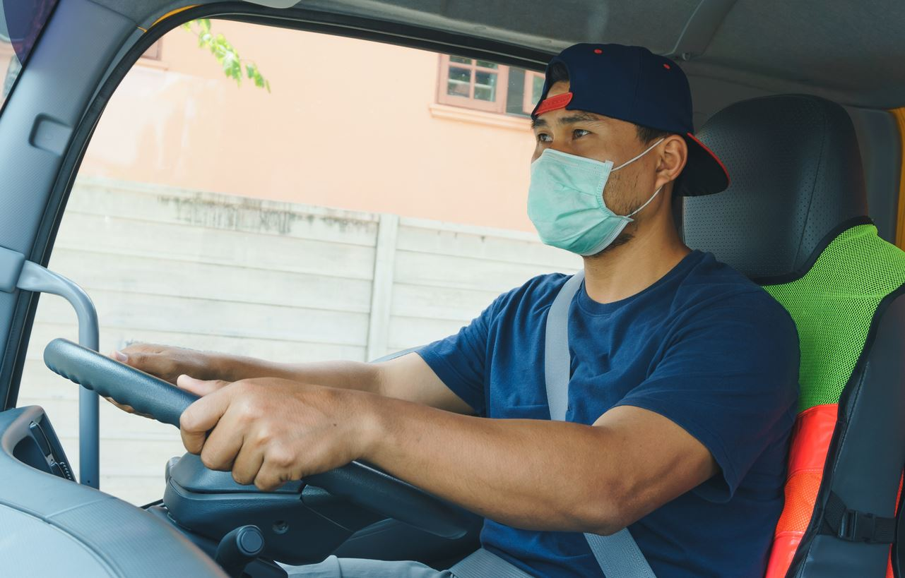 Truck Driver wearing mask while working to protect against the spread of COVID-19.
