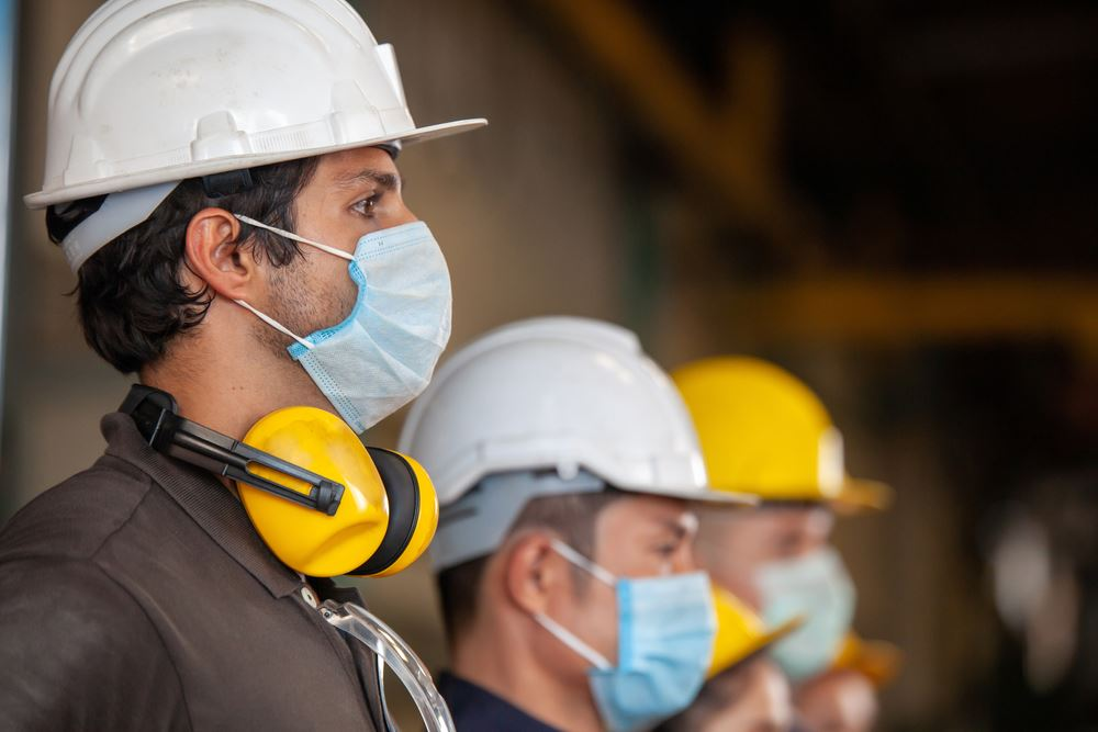 Workers wear protective face masks and distance themselves for safety in machine industrial factory.